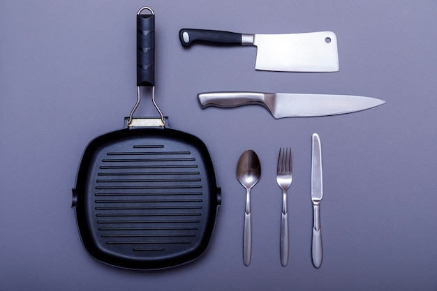Cuchillos de metal negro sobre una mesa gris, parrilla, toalla. lay flat, diseño.