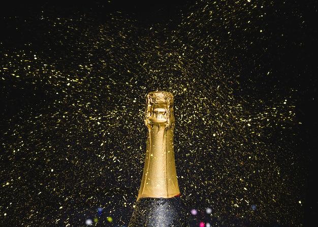 Cuello de botella de champagne con brillos voladores.