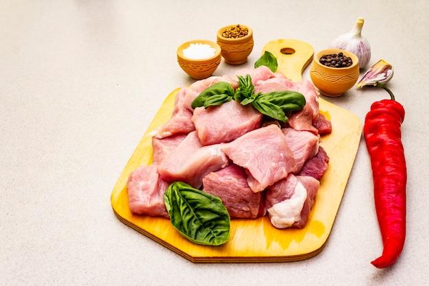Cuello de cerdo crudo, cortado en trozos con verduras frescas y especias secas.