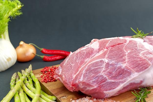 Cuello de cerdo crudo fresco con especias y verduras sobre tabla de madera