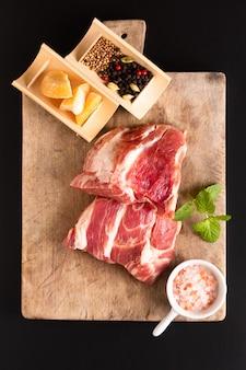 Cuello de cerdo deshuesado del pedazo del concepto de la comida en la tabla de cortar con la especia en fondo negro con el espacio de la copia
