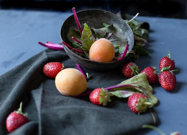 Cuenco con albaricoques y espinacas adentro y fresas afuera.