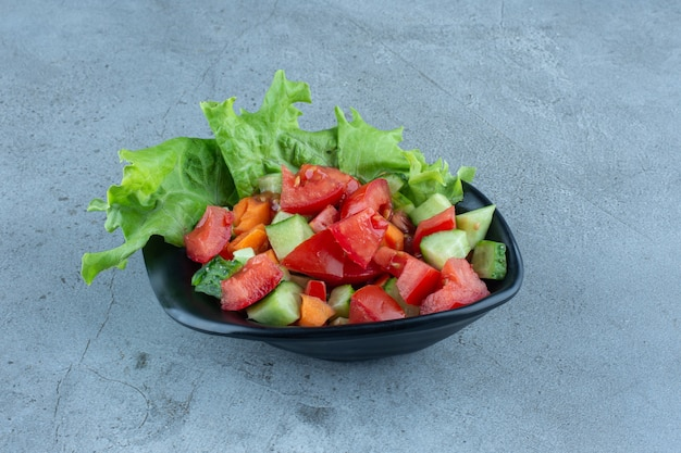 Cuenco de aperitivo con rodajas de pepino, tomate y zanahoria con hoja de lechuga sobre mármol.