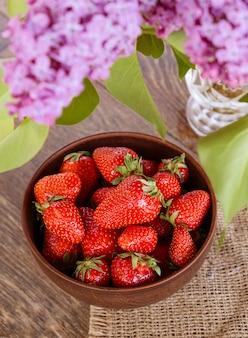 Cuenco de arcilla con fresa roja en mesa de madera.