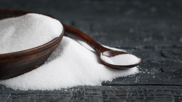 Cuenco de arcilla con sal marina blanca y cuchara de madera sobre la mesa.