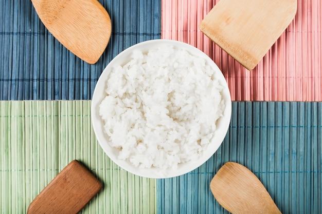 Cuenco de arroz al vapor blanco con diferentes tipos de espátula de madera en mantel colorido