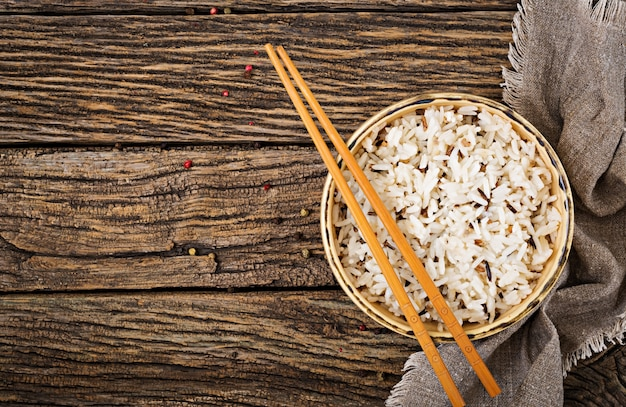 Cuenco con arroz hervido en una mesa de madera. comida vegana. comida dietética vista superior. lay flat