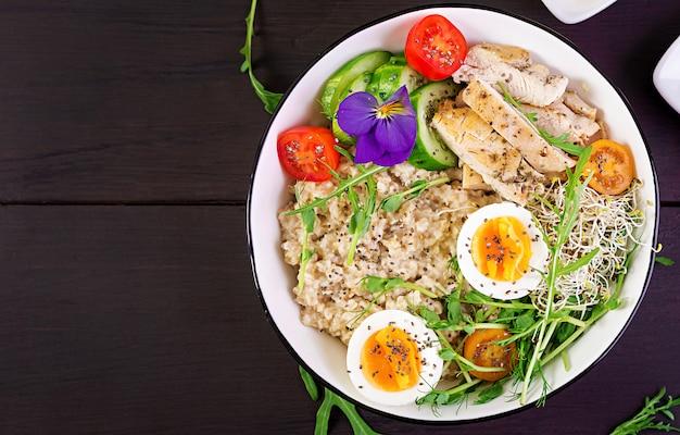 Cuenco con avena, filete de pollo, tomate, lechuga, microgreens y huevo cocido