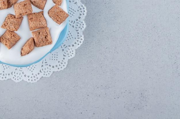Cuenco azul de copos de maíz de almohadillas de chocolate con espuma de crema. foto de alta calidad