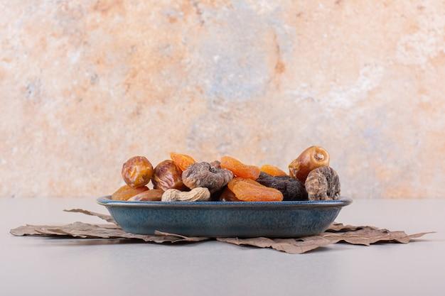 Cuenco azul de diversas frutas y frutos secos orgánicos sobre fondo blanco. foto de alta calidad