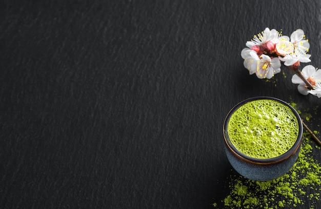 Cuenco de azul con té verde matcha, junto a una rama de cereza en flor y té en polvo sobre la mesa