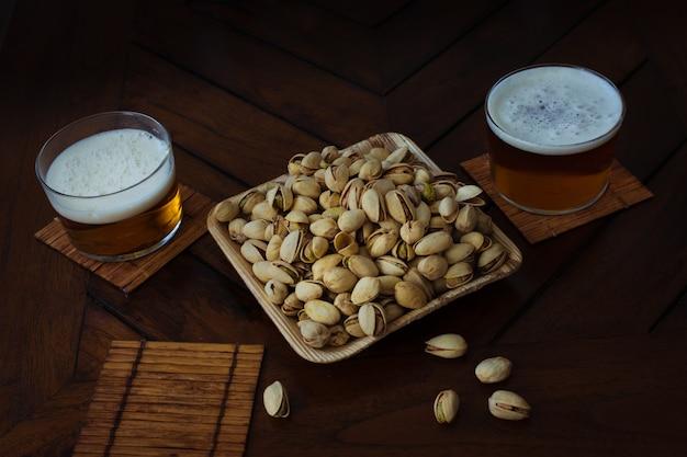 Cuenco de bambú lleno de pistachos y dos vasos de cerveza en un pub. mesa de madera. fiesta de verano de celebración.