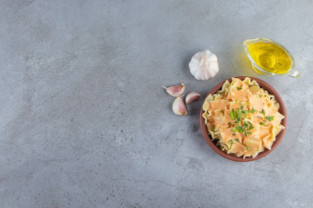 Cuenco de barro de deliciosos macarrones cremosos con aceite y verduras sobre fondo de piedra.