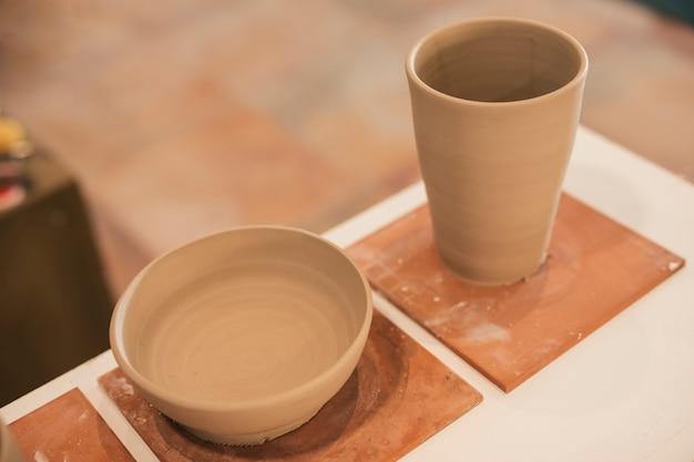 Cuenco de barro hecho a mano y vidrio en mesa