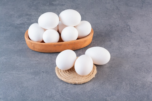 Cuenco de barro lleno de huevos blancos crudos sobre la mesa de piedra.