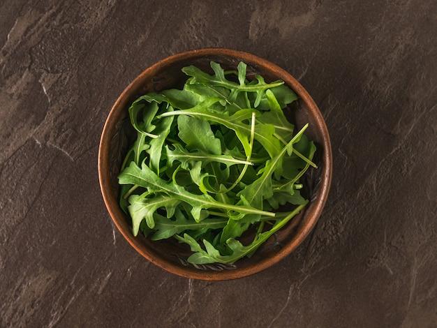 Cuenco de barro con rúcula fresca sobre una mesa de piedra. dieta saludable a base de plantas. cocina vegetariana.