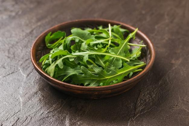 Cuenco de barro con rúcula fresca sobre una mesa de piedra oscura. dieta saludable a base de plantas. cocina vegetariana.
