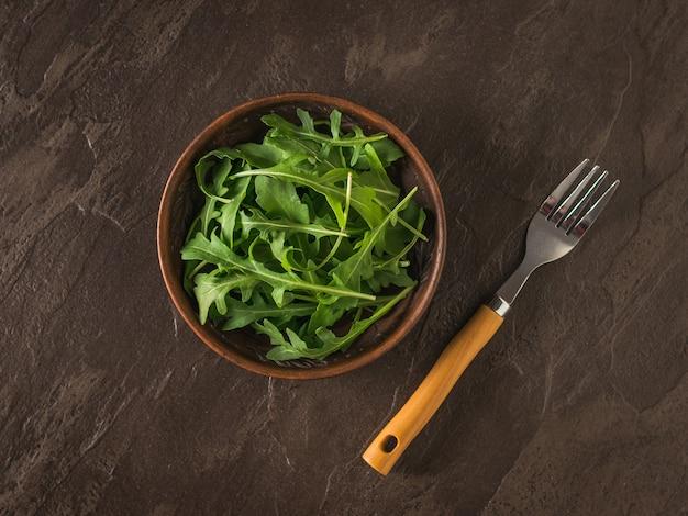 Cuenco de barro con rúcula fresca sobre una superficie de piedra. dieta saludable a base de plantas. cocina vegetariana. endecha plana.