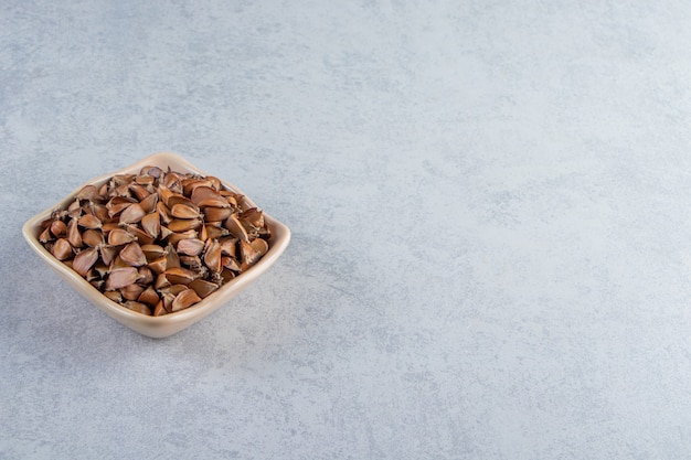 Cuenco beige de muchas semillas crujientes sobre fondo de piedra.