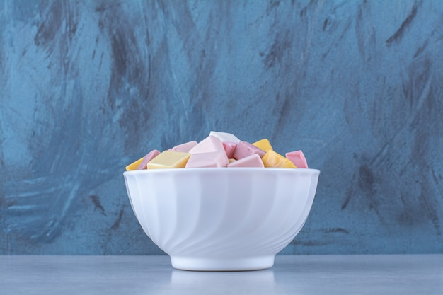 Un cuenco blanco con pastelería dulce rosa y amarilla pastila