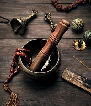 Cuenco cantor de cobre y un palo de madera en mesa marrón