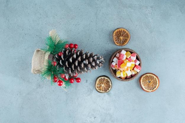 Cuenco de caramelos, rodajas de limón secas y decoración navideña en mármol.