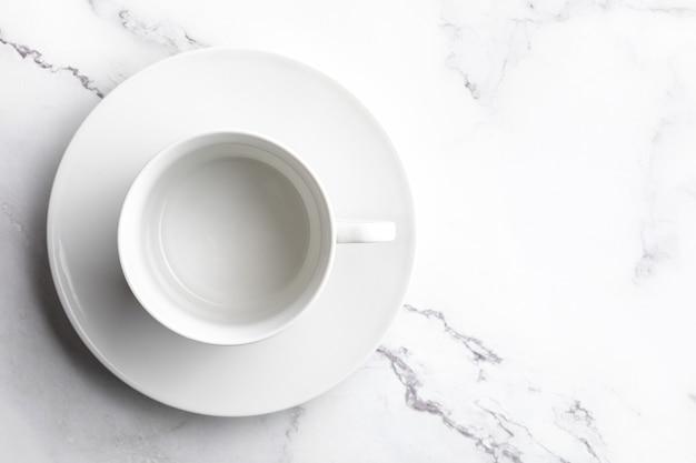 Cuenco de cerámica blanco vacío sobre fondo de mármol blanco.