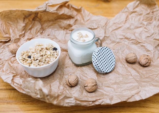 Cuenco de cereales; leche y nueces sobre papel marrón desmenuzado.
