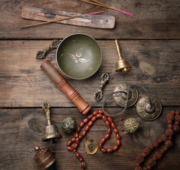 Cuenco de cobre, cuentas de oración, tambor de oración y otros objetos religiosos tibetanos para la meditación y la medicina alternativa.