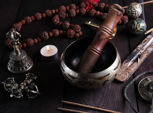 Cuenco de cobre y un palo de madera sobre una mesa marrón.