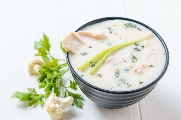 Un cuenco de crema de la sopa de la coliflor con caldo de pollo en una tabla blanca.