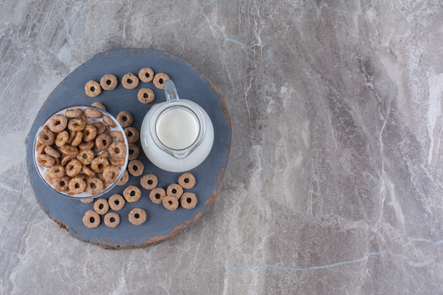 Un cuenco de cristal de yogur saludable con cereales crujientes y una jarra de cristal de leche.