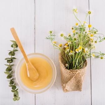 Cuenco de cuajada de limón y hermosas flores de manzanilla sobre fondo de madera