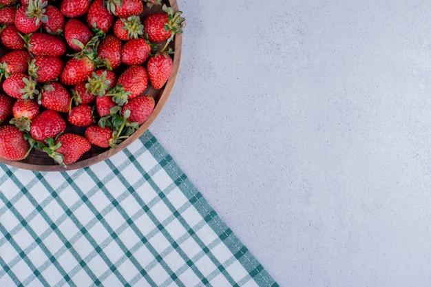 Cuenco grande lleno de fresas sobre fondo de mármol. foto de alta calidad