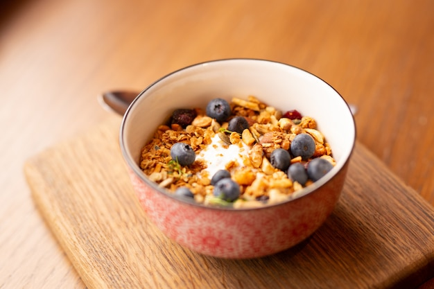 Cuenco de granola hecho en casa con yogur griego y arándanos sobre fondo marrón, vista superior. desayuno o merienda saludable
