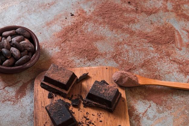 Cuenco de granos de cacao y polvo en cuchara con trozos de chocolate