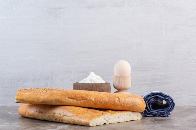 Cuenco de harina, soporte para huevos, rollo de mantel y panes tandoori sobre mármol.