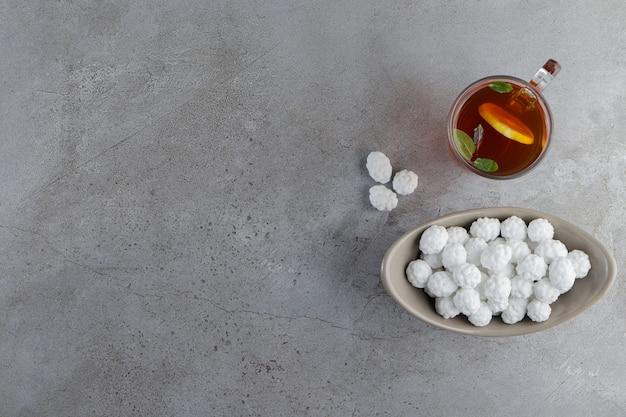 Un cuenco lleno de dulces caramelos blancos con una taza de té caliente sobre una mesa de piedra.