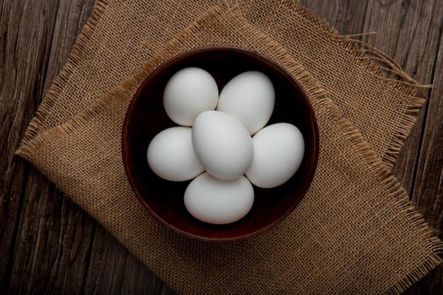 Cuenco lleno de huevos sobre superficie de tela de saco y mesa de madera