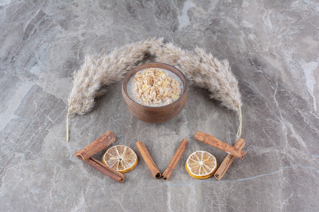 Un cuenco de madera de copos de maíz saludables con leche y palitos de canela.