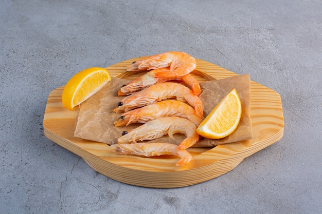 Un cuenco de madera de deliciosos camarones con rodajas de limón sobre un fondo de piedra.