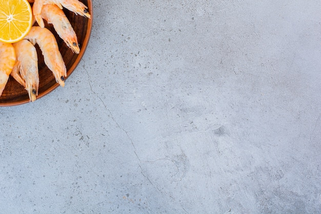 Un cuenco de madera de deliciosos camarones con rodajas de limón sobre una superficie de piedra