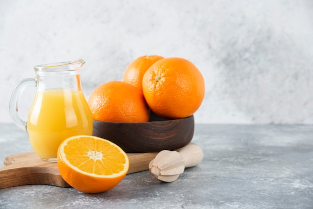 Un cuenco de madera con frutas naranjas frescas y una jarra de jugo de vidrio.