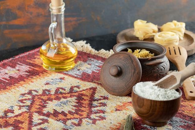Un cuenco de madera con harina y con una olla de pasta cruda