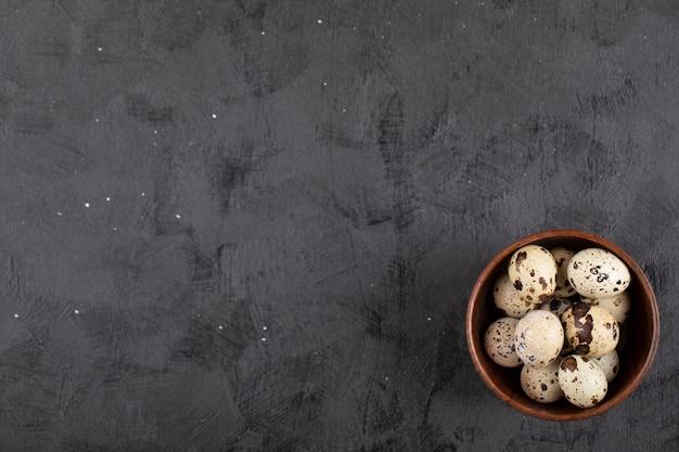Cuenco de madera de huevos de codorniz crudos orgánicos sobre superficie negra.