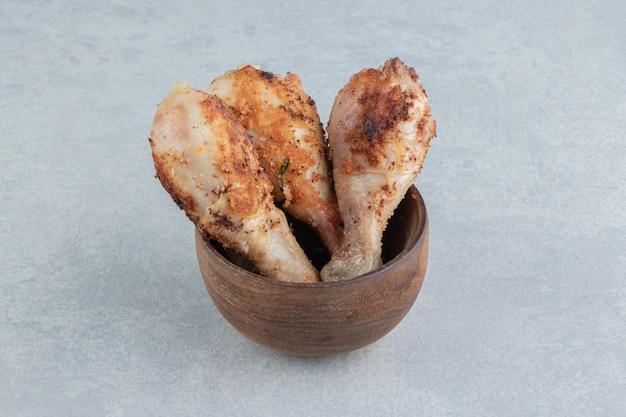 Un cuenco de madera lleno de carne de muslos de pollo al horno.