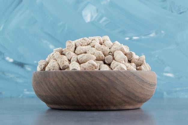 Un cuenco de madera lleno de cereales crujientes de centeno.