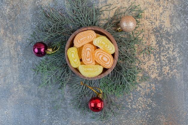 Un cuenco de madera lleno de gelatina de frutas dulces naranjas y amarillos. foto de alta calidad