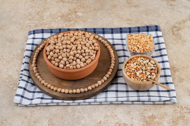 Un cuenco de madera lleno de guisantes sin preparar con especias y frijoles