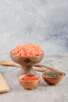 Cuenco de madera de macarrones crudos y especias sobre fondo de mármol
